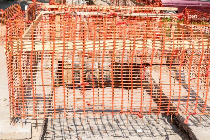Recinto arancio della rete di sicurezza del cantiere come barriera sopra la fossa sullo scavo della via immagine stock