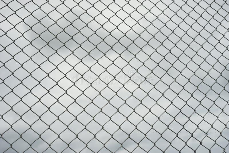 Recinto arrugginito della maglia del filo di acciaio, nuvola nel fondo immagine stock libera da diritti