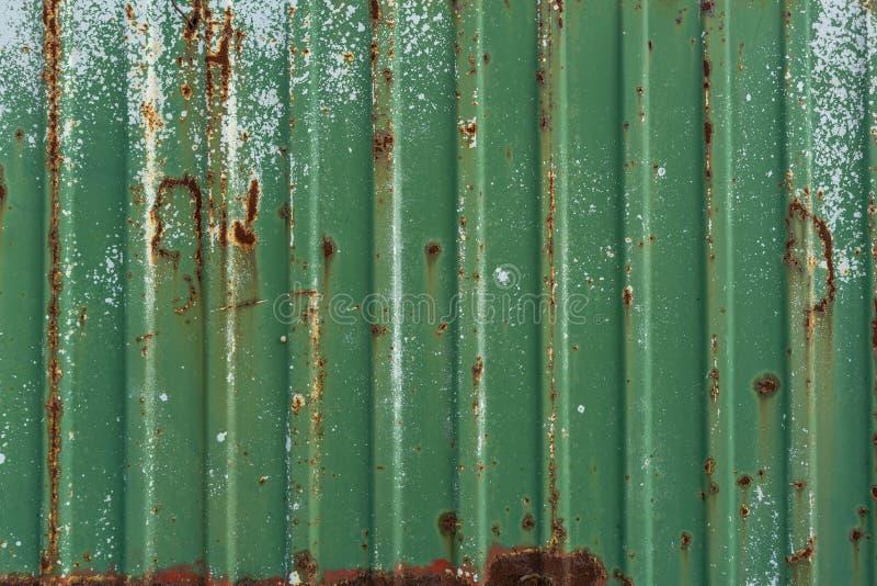 Recinto arrugginito verde del metallo Lamina di metallo ondulata Parete del container verde Fondo creativo d'annata fotografie stock