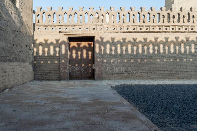 Recinto decorato dei mattoni della pietra vecchio con la porta e le ombre di legno delle decorazioni del recinto opposto, moschea immagine stock libera da diritti