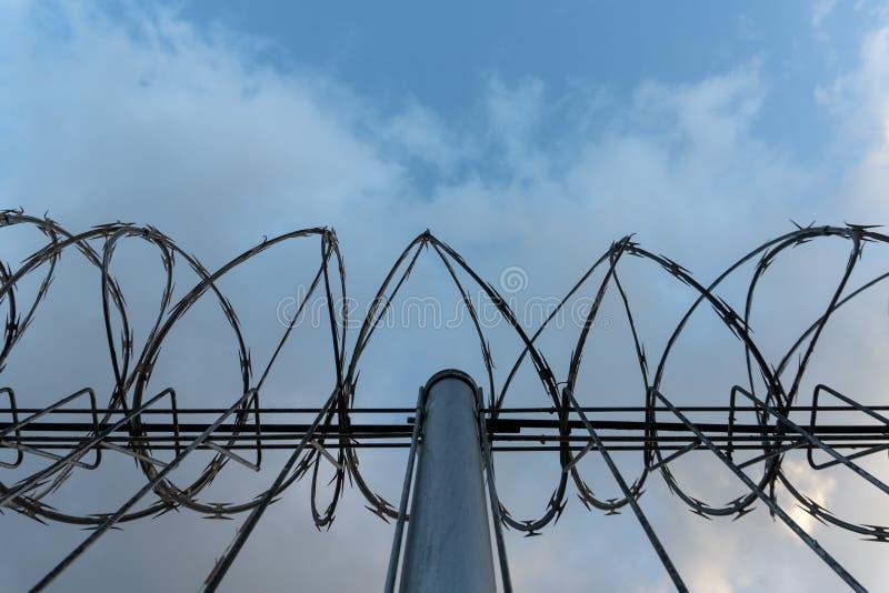 Recinto del filo spinato con cielo blu luminoso per ritenere silenzioso e solo e per volere libertà Nuvole drammatiche dietro il  fotografia stock