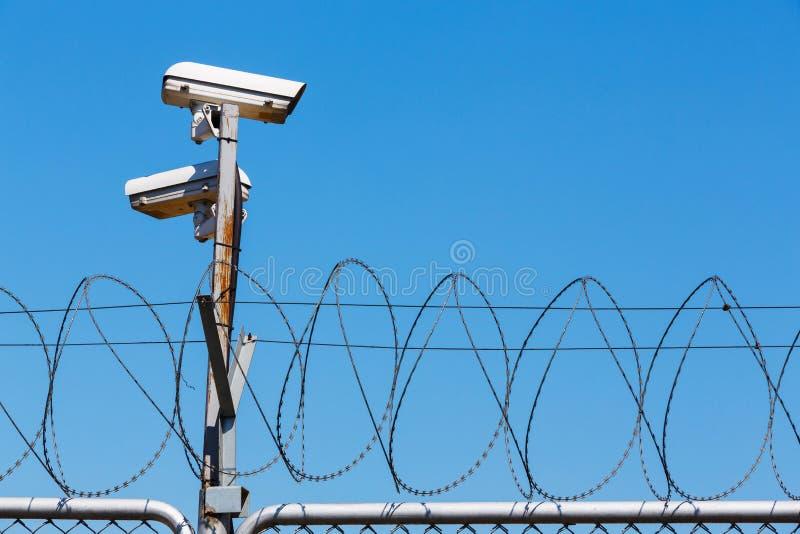 Recinto del filo spinato con la videocamera di sicurezza su cielo blu fotografia stock