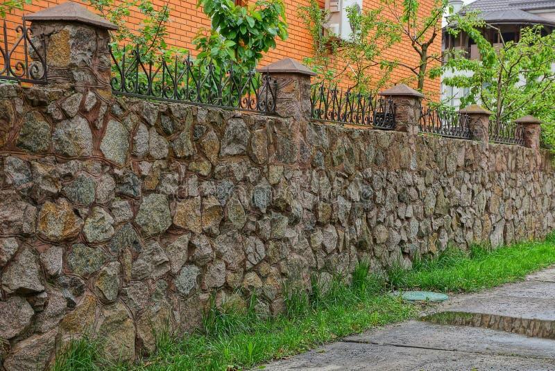 recinto di pietra marrone con i ramoscelli taglienti sulla via nell'erba verde dalla strada con le pozze immagini stock