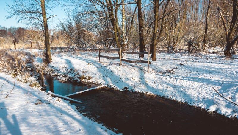 Recinto e fiume nella foresta di Snowy su Sunny Day fotografia stock