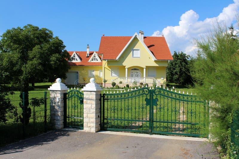 Recinto lavorato del metallo verde con le colonne di pietra davanti alla casa suburbana moderna della famiglia con il garage immagini stock libere da diritti