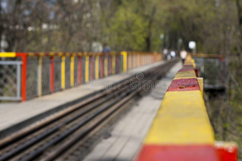 Recinto rosso e giallo di un ponte con la strada ferrata in primavera di un giorno soleggiato fotografia stock