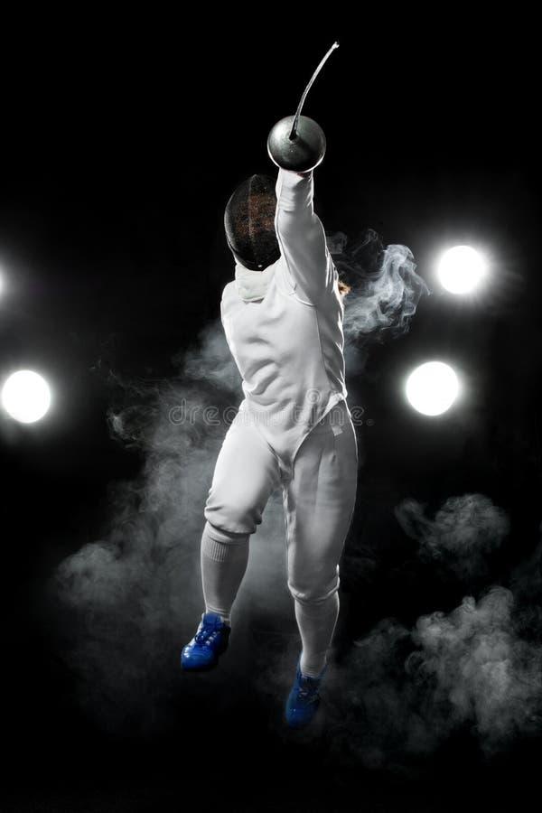 Recinzione del giocatore dell'atleta con la rapière sui precedenti neri fotografie stock
