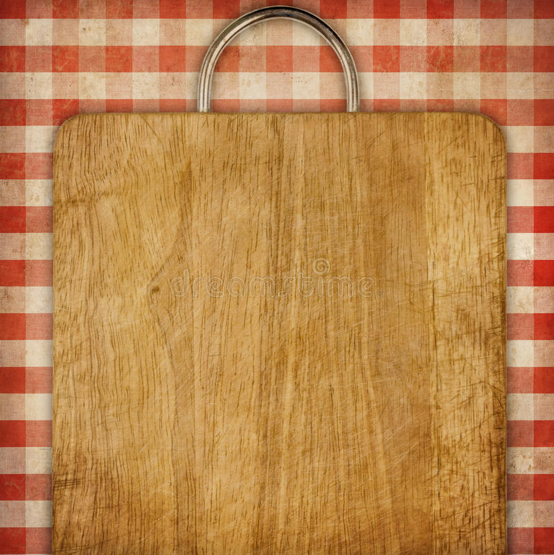 Recipe background breadboard over red gingham picnic tablecoth. Hardboard or breadboard over red checked gingham picnic tablecloth grunge background stock photography
