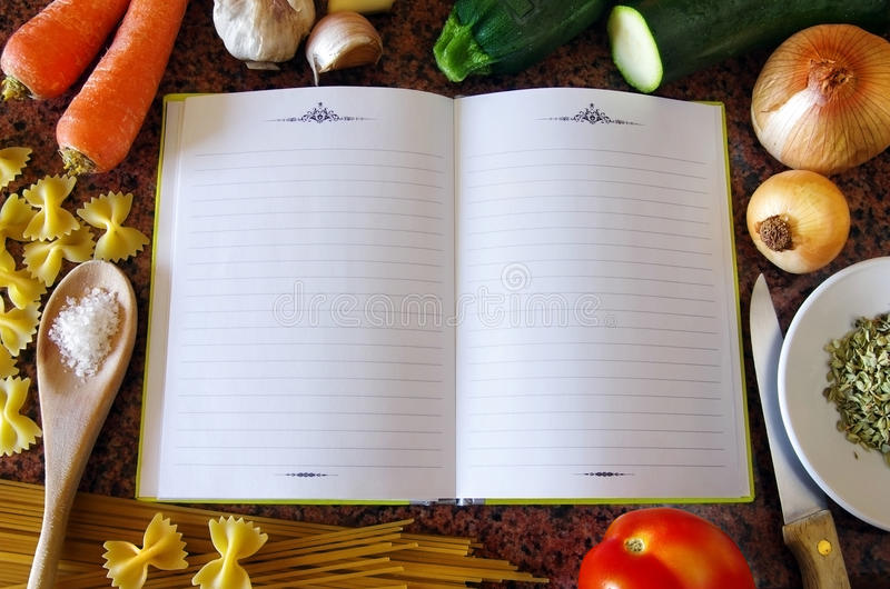 Recipe Book. Top view of an empty recipe book surrounded of food ingredients and kitchen utensils royalty free stock image