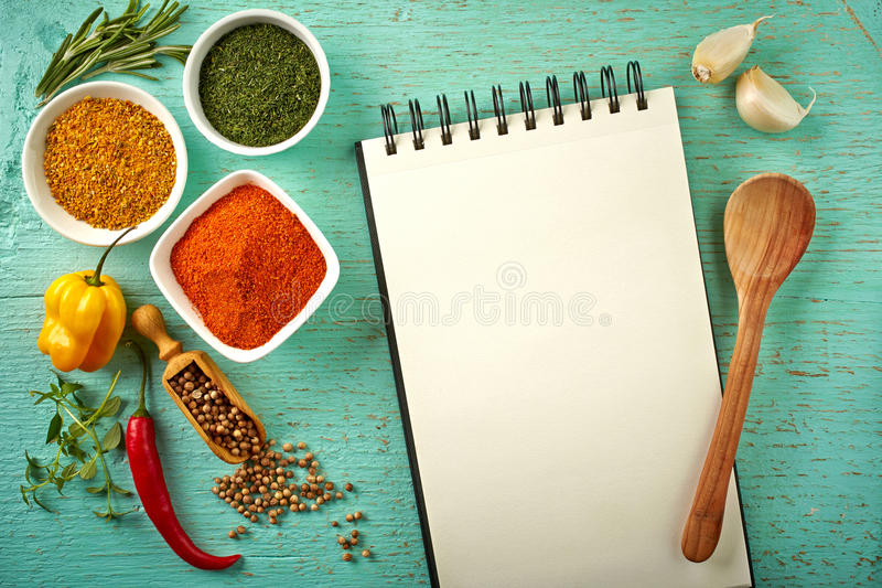 Recipe book. And various spices on blue wooden background royalty free stock photos