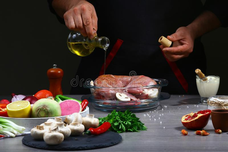 Recipe for cooking rabbit meat. Chef pouring oil on rabbit meat, cooking process, restaurant concept stock photos