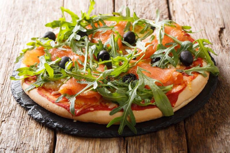 Recipe for delicious Italian pizza with salmon, arugula, black olives and mozzarella cheese close-up. horizontal. Recipe for delicious Italian pizza with salmon stock photo