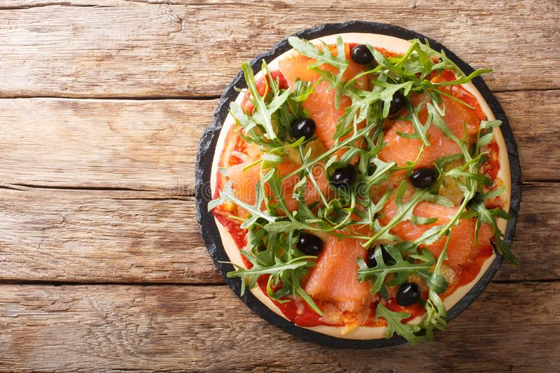 Recipe for delicious Italian pizza with salmon, arugula, black olives and mozzarella cheese close-up. horizontal top view. Recipe for delicious Italian pizza stock photography