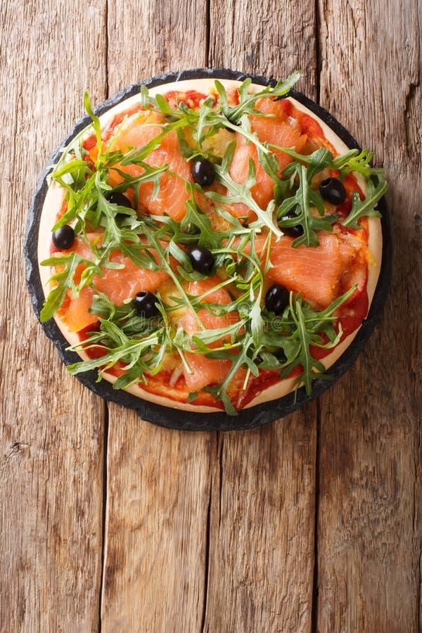 Recipe for delicious Italian pizza with salmon, arugula, black olives and mozzarella cheese close-up. Vertical top view. Recipe for delicious Italian pizza with stock image