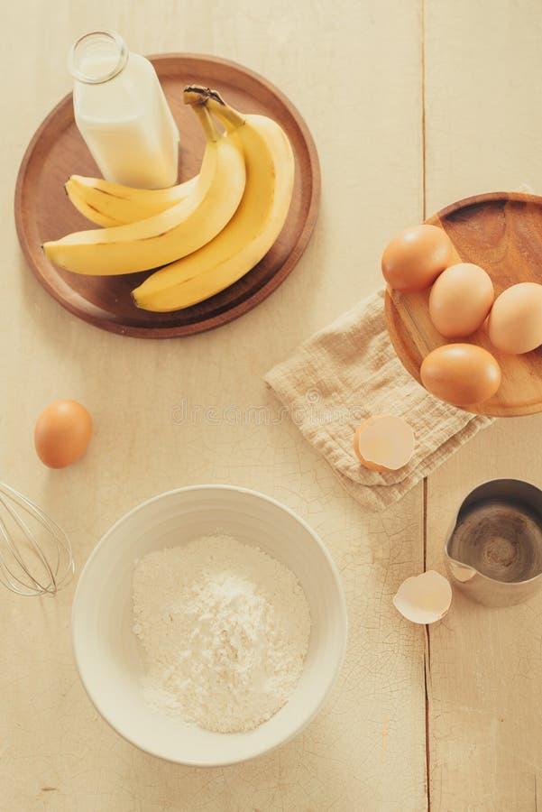 Baking cake in rural kitchen - dough recipe ingredients eggs, flour, sugar on vintage wooden table.  royalty free stock photo