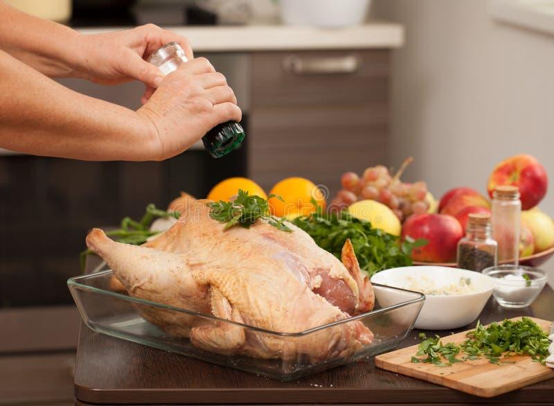 A woman sprinkles salt on the Turkey for roasting royalty free stock photos