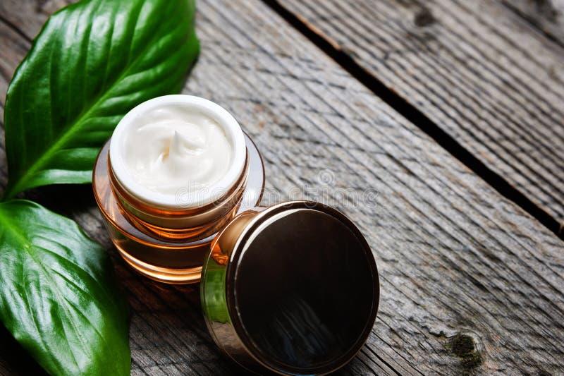 Recipiente cosmético com as folhas ervais verdes, etiqueta vazia da garrafa para o modelo de marcagem com ferro quente, fotografia de stock royalty free