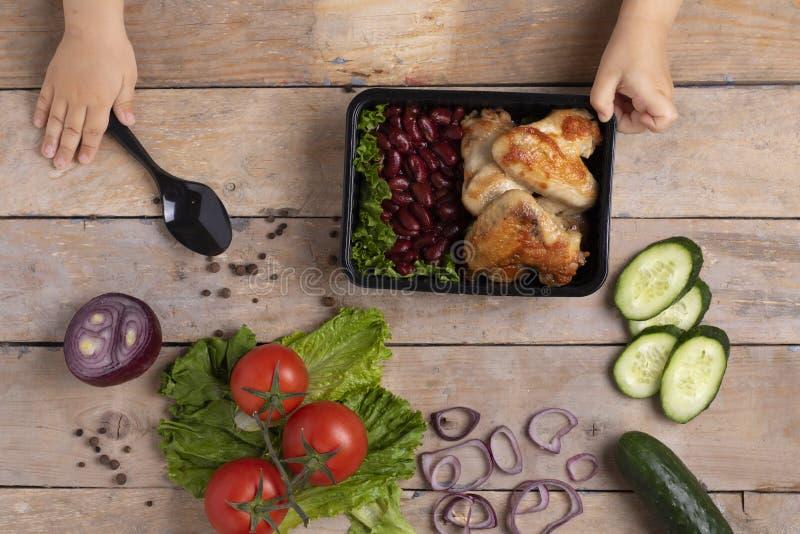 Recipiente de alimento do preto da terra arrendada da menina com jantar, vista superior fotos de stock