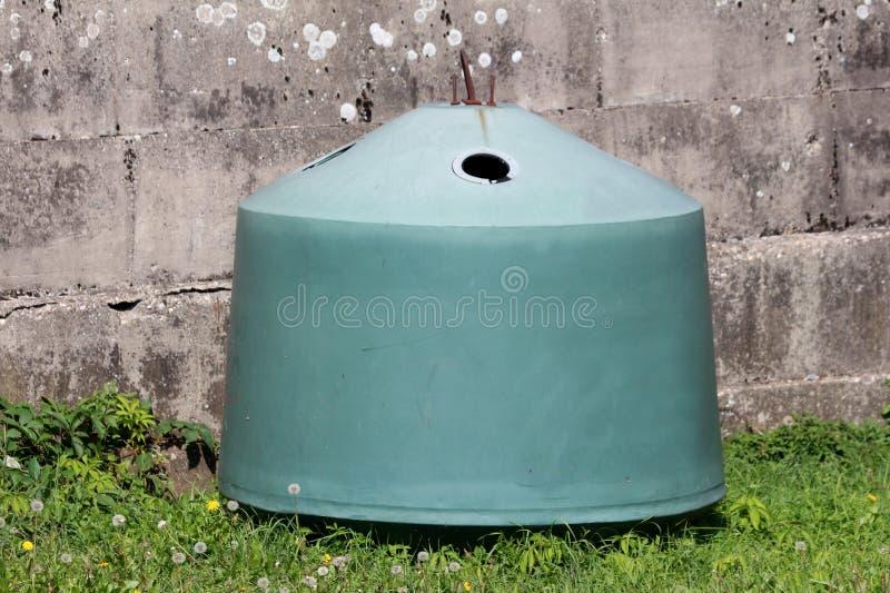 Recipiente de lixo de vidro com cor verde desvanecida e gancho oxidado do metal na parte superior na frente do muro de cimento na imagem de stock