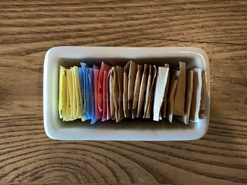 Recipiente de pacotes do substituto do açúcar do nd do açúcar em uma tabela do restaurante fotos de stock