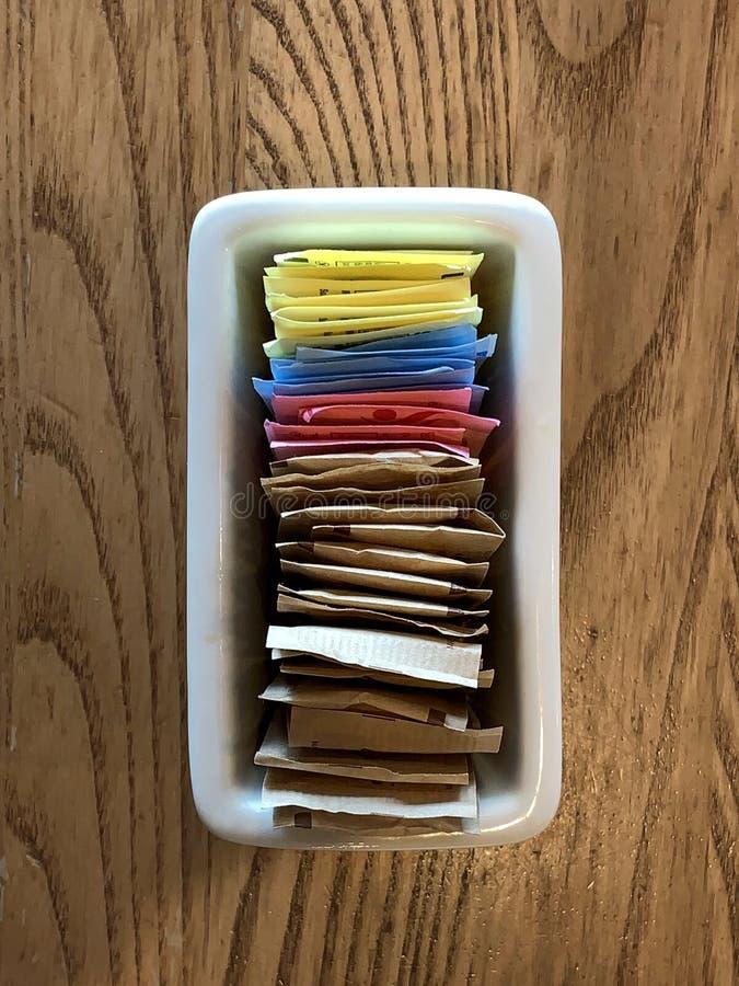 Recipiente de pacotes do substituto do açúcar do nd do açúcar em uma tabela do restaurante fotografia de stock royalty free