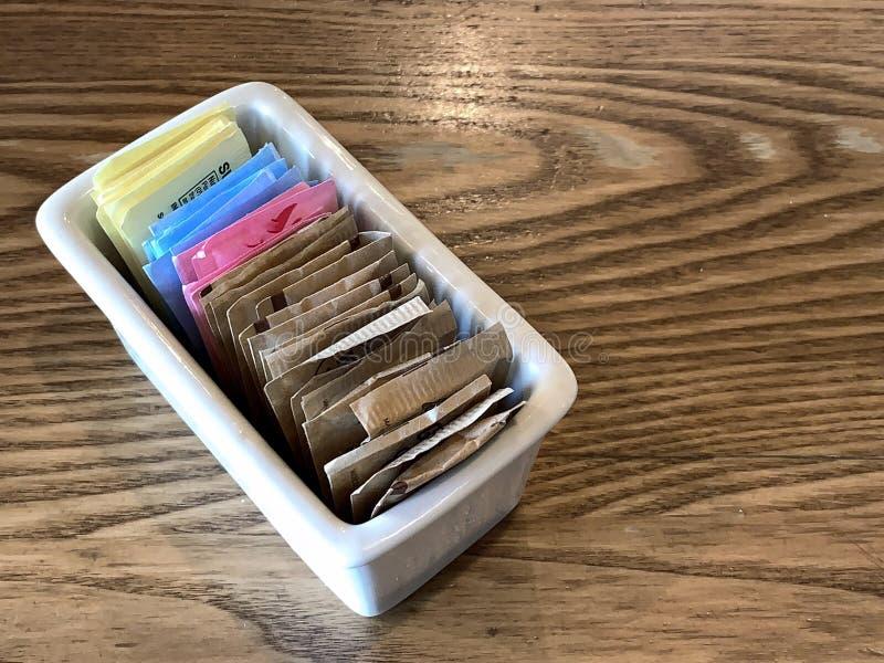 Recipiente de pacotes do substituto do açúcar do nd do açúcar em uma tabela do restaurante foto de stock
