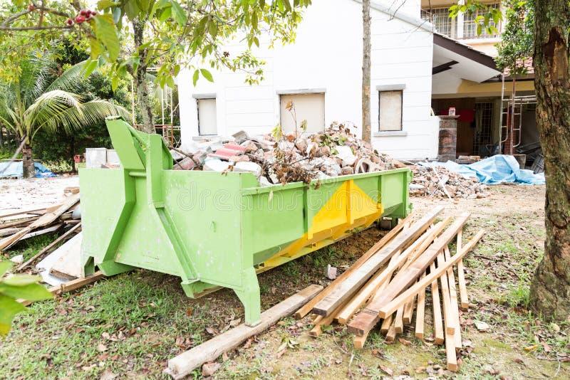 Recipiente dei rifiuti della costruzione con i carichi al cantiere immagini stock libere da diritti
