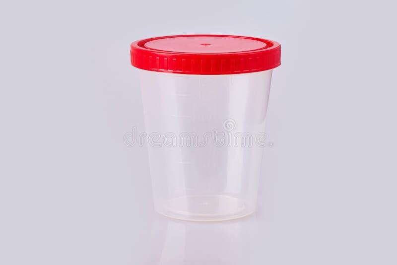 Recipiente di plastica in bianco trasparente per urina con lo spiritello malevolo isolato immagine stock libera da diritti