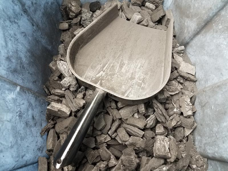 Recipiente di plastica sporco con i pezzi del carbone ed il mestolo neri del metallo immagine stock