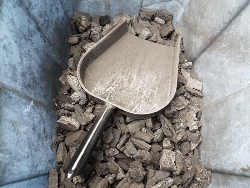Recipiente di plastica sporco con i pezzi del carbone ed il mestolo neri del metallo immagini stock libere da diritti