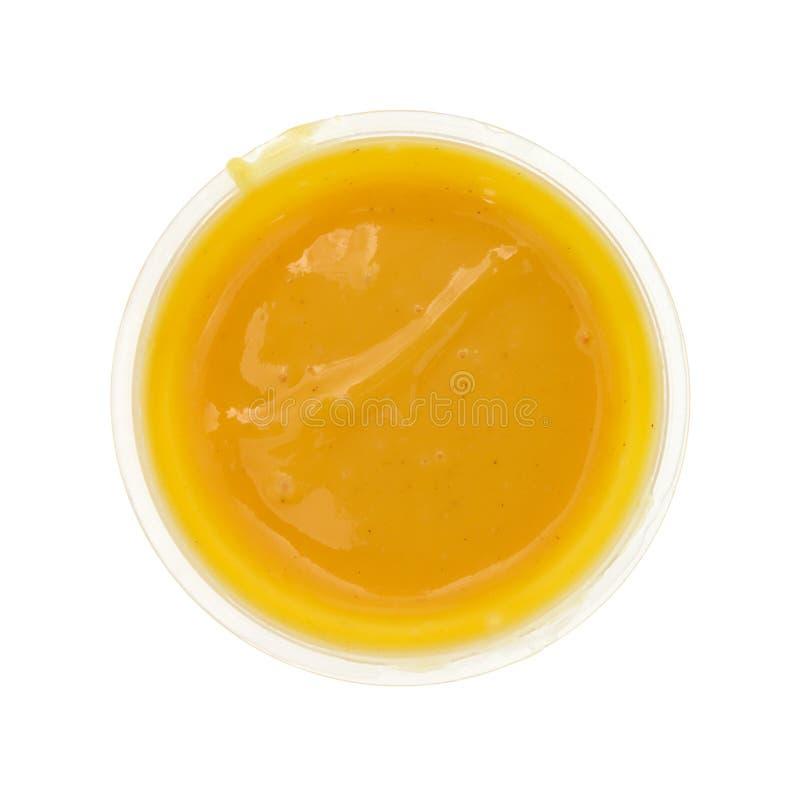 Recipiente do molho da mostarda do mel em um fundo branco imagens de stock