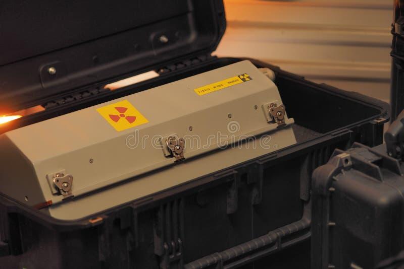 Recipiente em forma de caixa do metal com aviso da radiação em uma caixa militar do transporte da categoria sob a luz vermelha fotos de stock