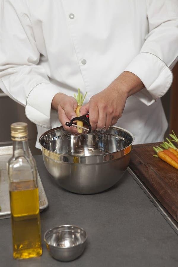 Recipiente masculino de Peeling Carrots In do cozinheiro chefe fotos de stock royalty free