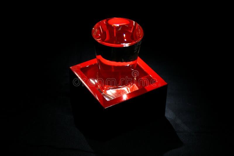 Recipiente, masu, e vidro vermelhos envernizados para a causa bebendo ou de medição no fundo preto imagem de stock royalty free