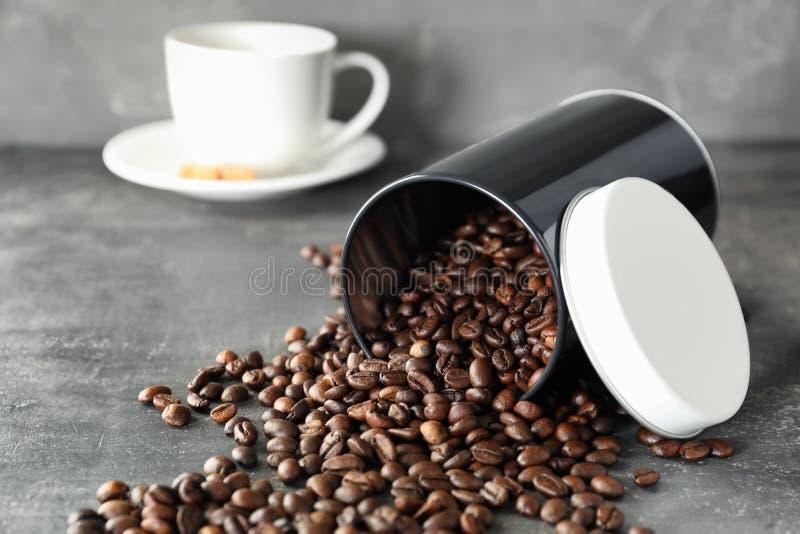 Recipiente virado com os feijões de café roasted na tabela fotos de stock royalty free