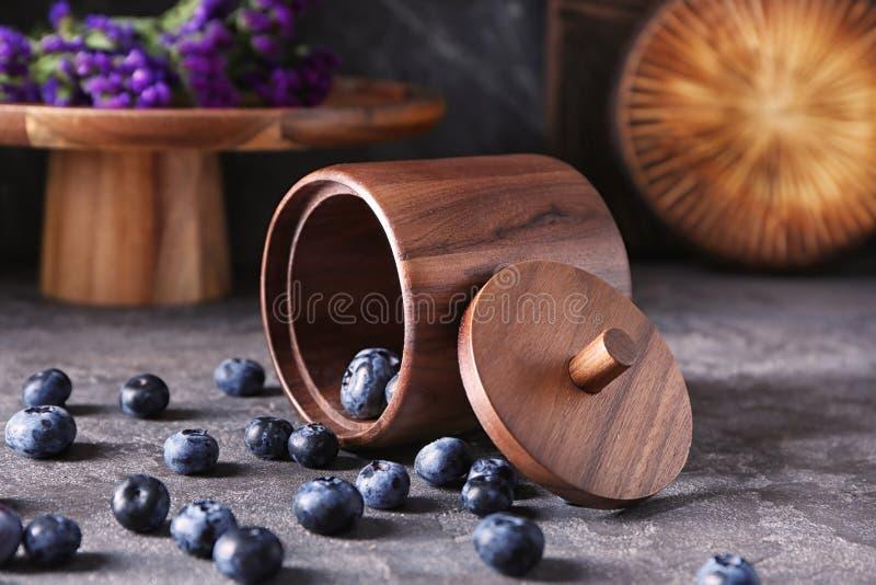Recipiente virado com os mirtilos deliciosos na tabela cinzenta foto de stock royalty free