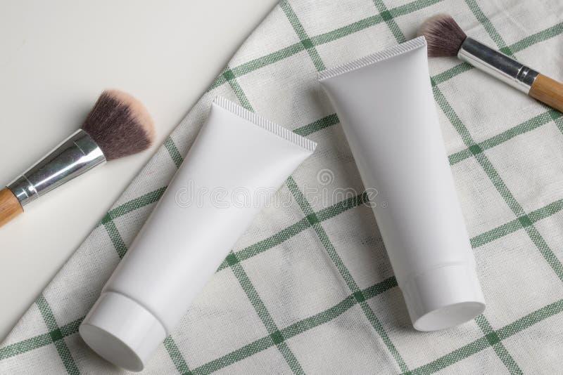 Recipientes cosméticos da garrafa com as folhas ervais verdes, etiqueta vazia fotografia de stock