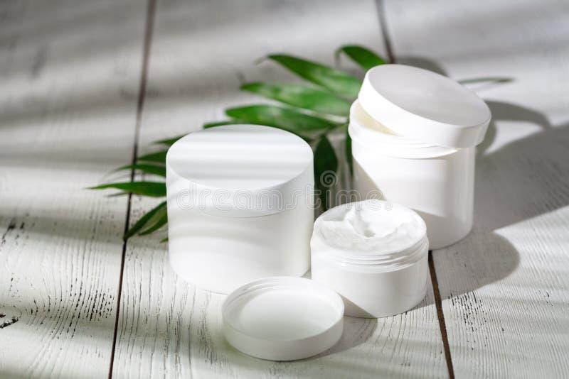 Recipientes cosméticos da garrafa com as folhas ervais verdes, etiqueta vazia foto de stock royalty free