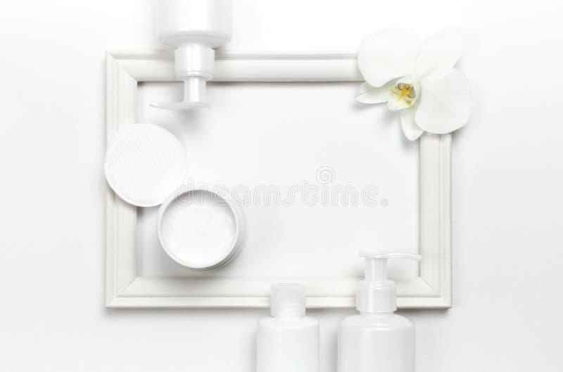 Recipientes da garrafa, mão ou creme de corpo cosmético branco, flor da orquídea, quadro da foto na configuração lisa clara da op foto de stock royalty free