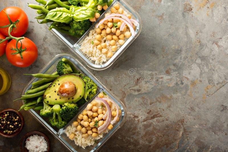 Recipientes da preparação da refeição do vegetariano com arroz e os grãos-de-bico cozinhados imagens de stock