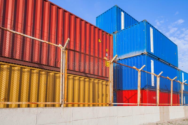 Recipientes de carga industriais coloridos atrás da cerca do metal imagens de stock royalty free