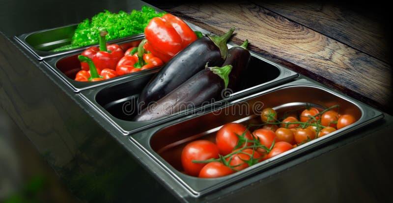 Recipientes do ferro na cozinha com vegetais imagens de stock