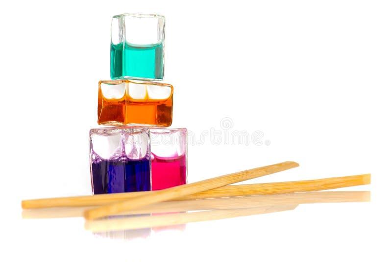 Recipientes líquidos coloridos ao lado das varas chinesas isoladas no branco imagem de stock