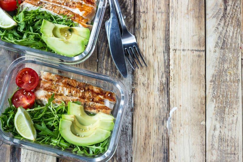 Recipientes saudáveis da preparação da refeição com rukola, grade do peru, tomates e abacate foto de stock