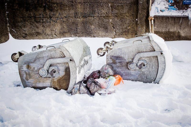 Recipientes virados do lixo durante o inverno forte e nevado fotografia de stock