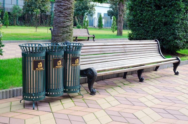 Recipienti della grata del ferro dell'immondizia per la separazione dell'immondizia in un parco della città accanto al banco immagini stock