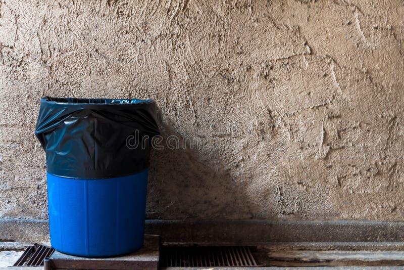 Recipienti di riciclaggio sulle grondaie di drenaggio con le vecchie pareti del gesso immagini stock libere da diritti