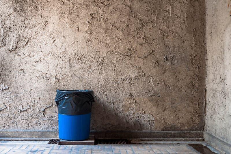 Recipienti di riciclaggio sulle grondaie di drenaggio con le vecchie pareti del gesso immagine stock libera da diritti