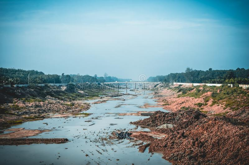 Reclamation soil from water reservoir or along deep canal in rural area. Water irrigation management work concept. Outdoor with bright sunlight on summer day stock images