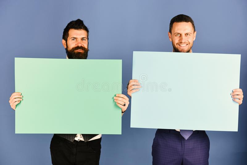Reclame of commerciële affiches De mensen met baarden houden raad op blauwe achtergrond royalty-vrije stock foto's